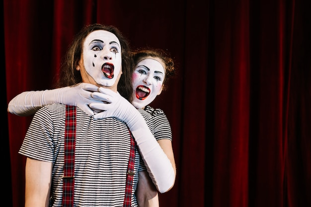 Female mime artist grabbing male mime's neck Free Photo