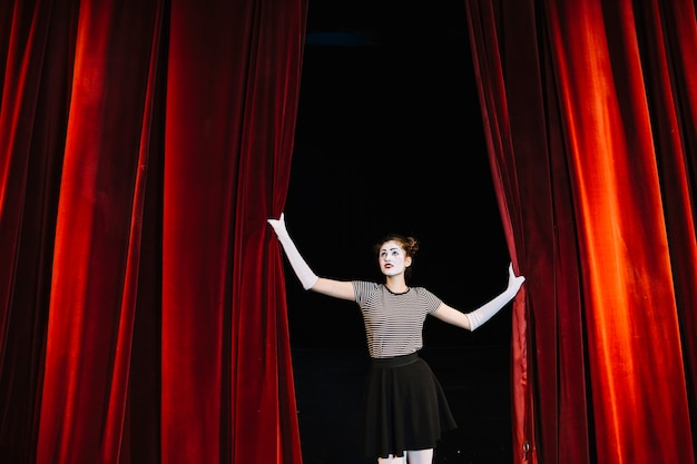 Female mime artist holding red curtain Free Photo