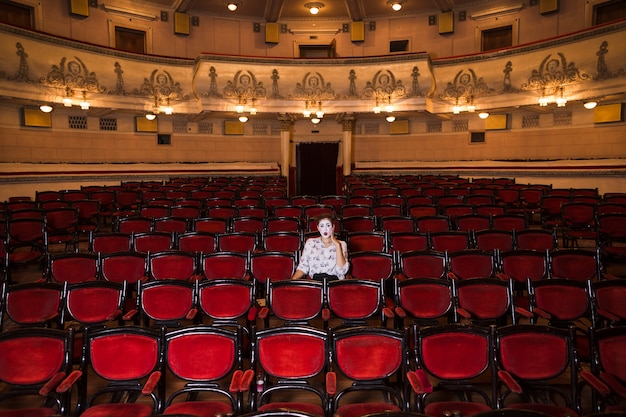 Female mime artist sitting alone in an auditorium Free Photo