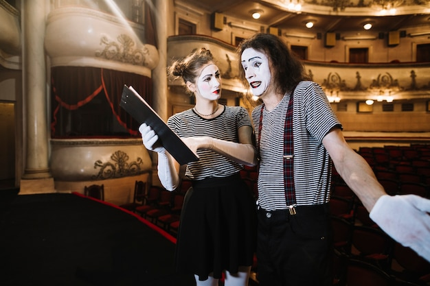 Female mime assisting male mime while performing on stage Free Photo