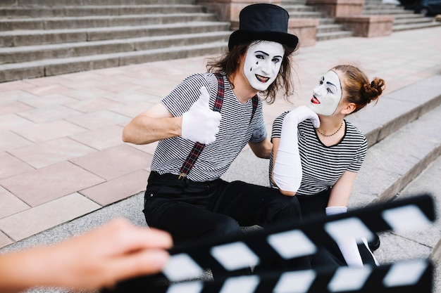 Female mime looking at male mime gesturing thumbs up Free Photo