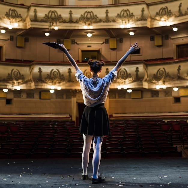 Female mime raising her arms in auditorium Free Photo
