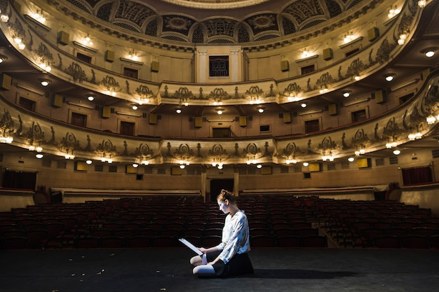 Female mime sitting on stage reading manuscript Free Photo