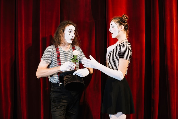 Female mime taking white rose from male mime standing in front of red curtain Free Photo