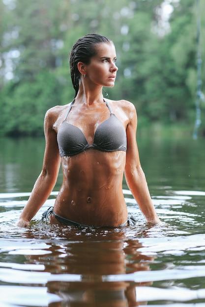 Modello femminile in costume da bagno nero nel lago Foto Gratuite