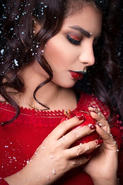 ザクロを保持している赤いドレスの女性モデル 無料写真
