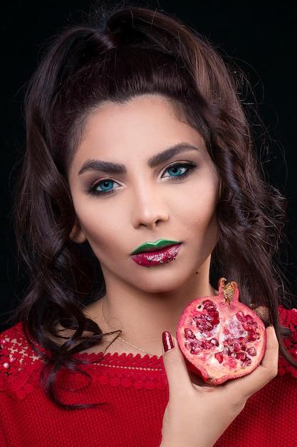 ザクロを保持している赤い口紅の女性モデル 無料写真