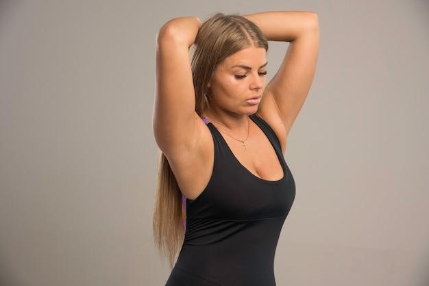 スポーツブラの女性モデルは、頭の後ろに手を置きます。 無料写真