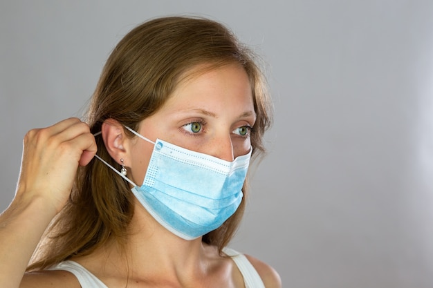 수술 얼굴 마스크를 부착하는 흰 셔츠에 여성 모델 프리미엄 사진