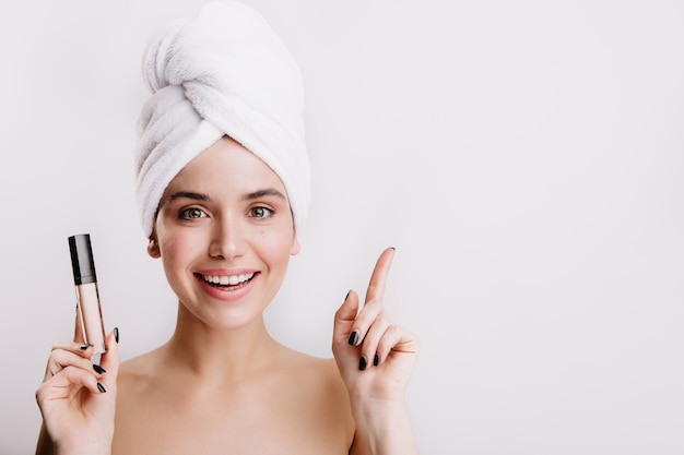 Female model knows how to hide imperfections on face and with smile demonstrates skin corrector. Free Photo