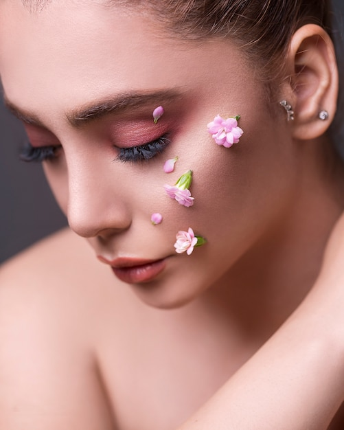 Female model with flowers in her face Free Photo