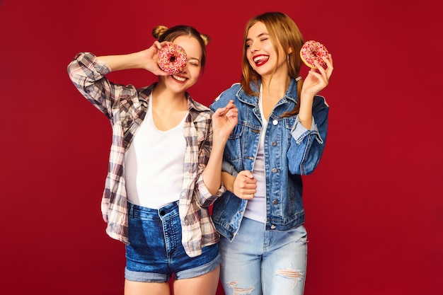 Female models holding pink donuts with sprinkles Free Photo