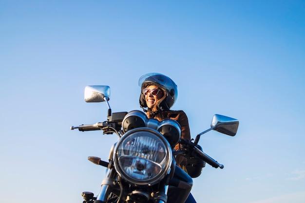ヘルメットをかぶってレトロなスタイルのオートバイに乗る女性のバイクライダー 無料写真
