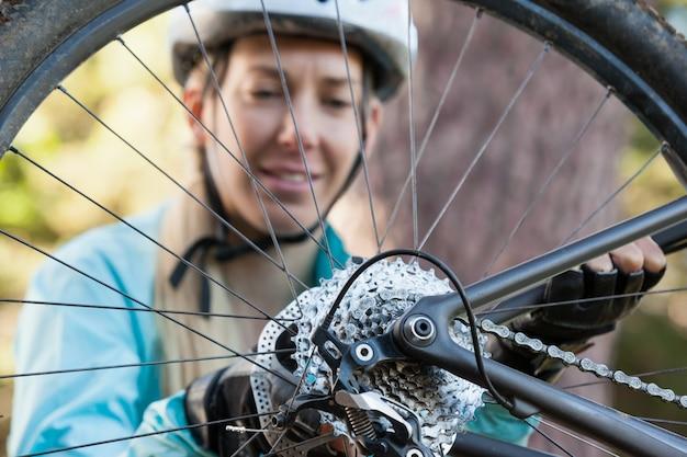 Женский горный велосипедист осматривает колесо своего велосипеда Premium Фотографии