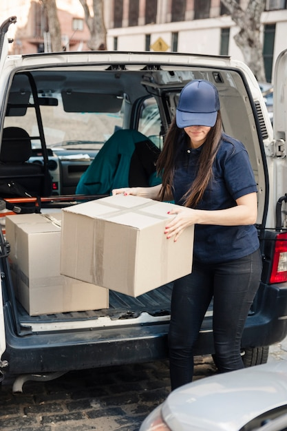 Female mover unloading cardboard boxes from vehicle Free Photo