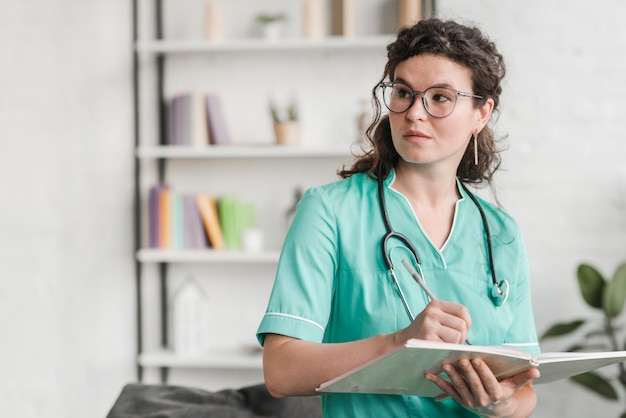 Female nurse holding book and pen wearing glasses looking away Free Photo
