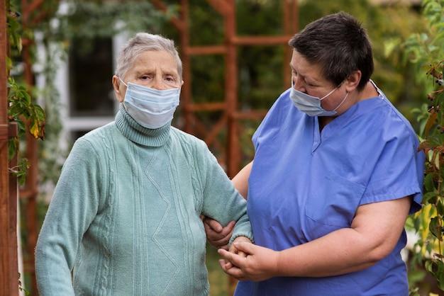 Infermiera femminile che si prende cura della donna anziana con mascherina medica Foto Gratuite