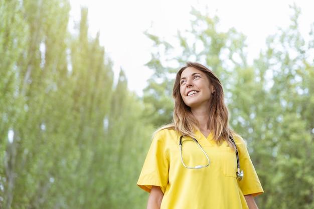 空を見ている聴診器を持つ女性看護師 Premium写真