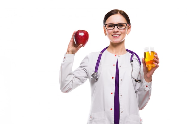 Female nutritionist holding apple and glass of fresh juice in her hands on white Premium Photo