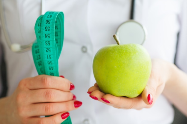 Female nutritionist and holding an apple and a measure tape. new start for healthy nutrition, body slimming, weight loss. cares about body Premium Photo