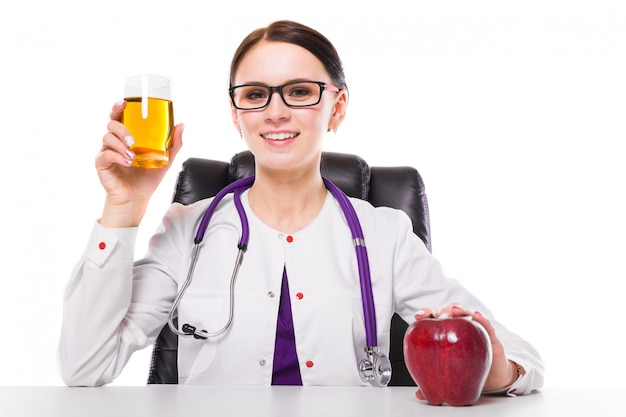 Female nutritionist sitting in her working place showing and offering glass of apple fresh juice holding apple in her hand on white Premium Photo