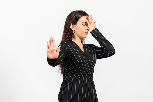 Impiegato femminile in abito nero rigoroso non vuole guardare su bianco Foto Gratuite