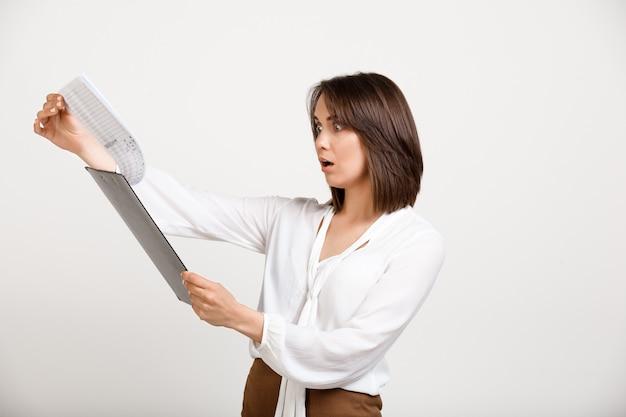 Женский офисный работник читает отчет Бесплатные Фотографии
