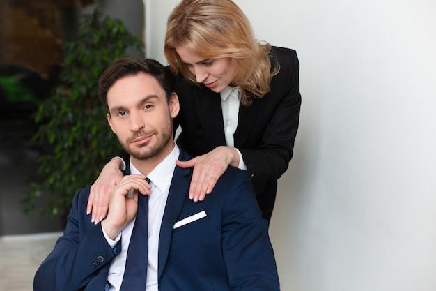 여성 회사원이 남성 상사에게 유혹합니다. 남성 어깨를 쓰 다듬어 젊은 여자. 여성 권한 부여 프리미엄 사진
