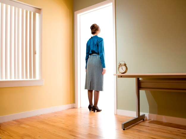 Female office worker standing in an office doorway looking into a room illuminated with light Premium Photo