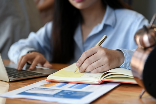 Female office workers using laptop and writing notes. Premium Photo