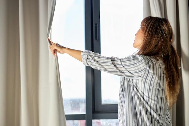 Женщина открывает шторы утром после пробуждения, в пижаме Premium Фотографии