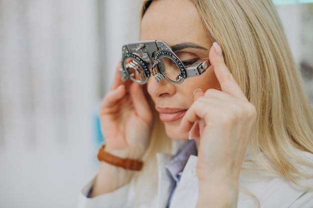 Женский оптик, измеряющий ее зрение Бесплатные Фотографии