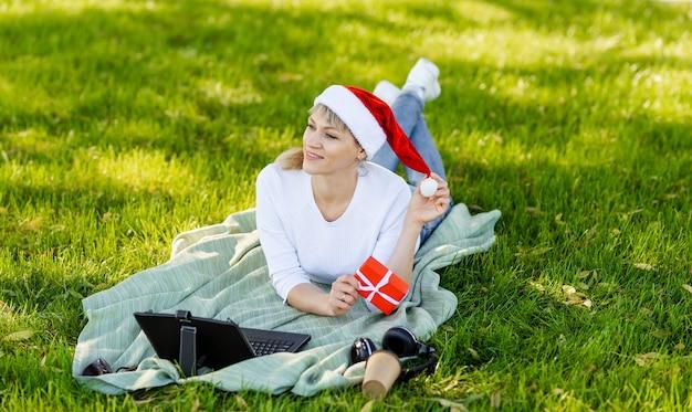 Женщина заказывает подарки на ноутбуке и пьет кофе. счастливая женщина покупает рождественские подарки онлайн. девушка делает покупки в интернете на компьютере. серфинг и шоппинг. веселого рождества и счастливого нового года Premium Фотографии