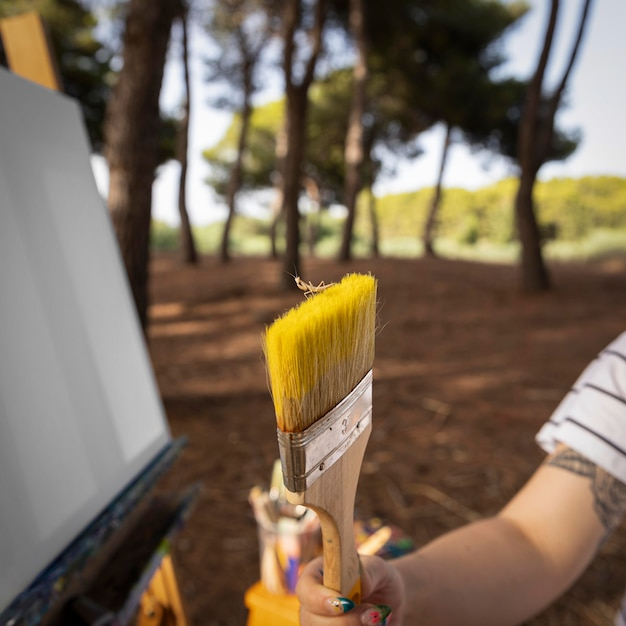 ブラシを保持している屋外の女性画家 無料写真