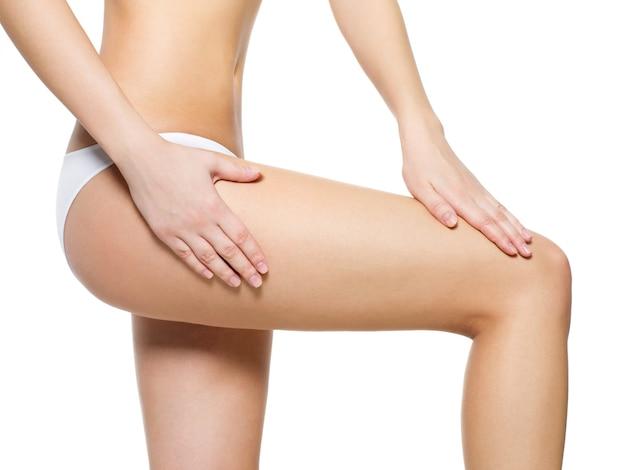 Женщина балует целлюлитную кожу на ногах - снимок крупным планом на белом пространстве Бесплатные Фотографии