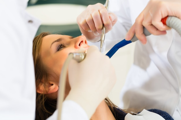 Female patient with dentist and assistanta dental treatment, wearing masks and gloves Premium Photo