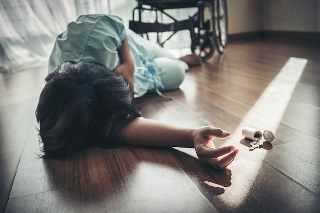 Female patients fall unconscious from a wheelchair on the floor Premium Photo