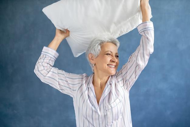 Пенсионерка в шелковистой пижаме смеется, находится в хорошем настроении, веселится в спальне, поднимает руки, держит над головой перьевую подушку Бесплатные Фотографии
