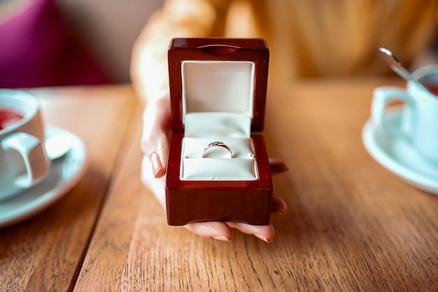 女性の人の手は黄金の結婚指輪のクローズアップビューでボックスを保持します Premium写真