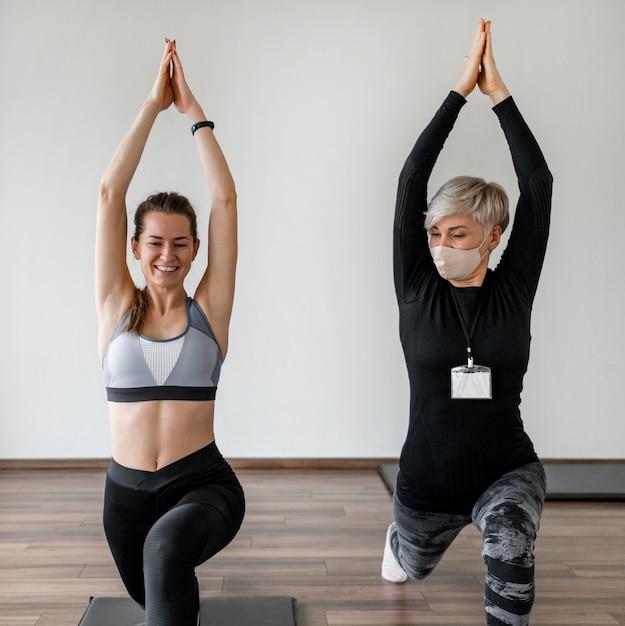 ヨガの練習をしている女性のパーソナルトレーナーとクライアント 無料写真