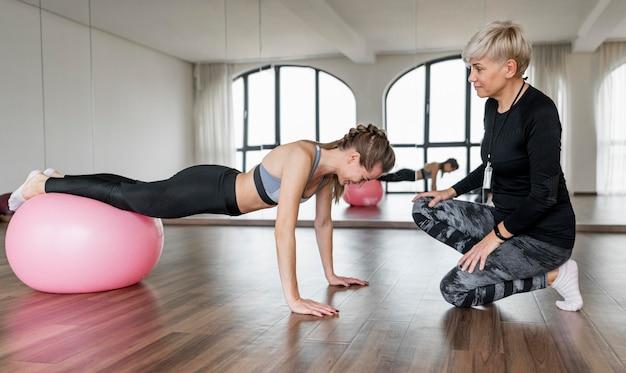 フィットネスボールを使用する女性のパーソナルトレーナーとクライアント 無料写真