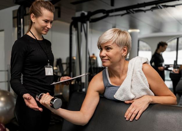 ダンベルを使用している女性のパーソナルトレーナーと彼女のクライアント 無料写真