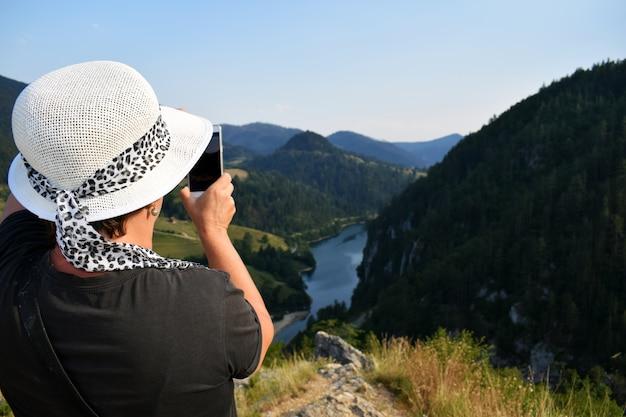 美しい屋外設定で撮影している女性の写真家。 Premium写真
