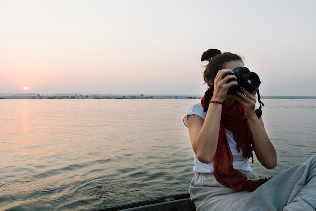 Female photographer sitting on a boat on the river ganges Free Photo