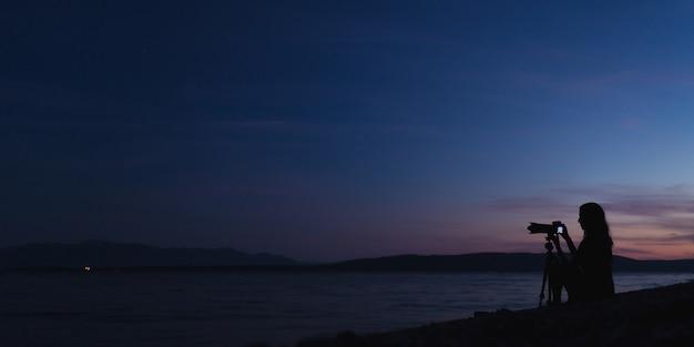 夕暮れ時にビーチで写真を撮る女性写真家 Premium写真