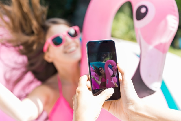 Female photographing beautiful teen woman on inflatable flamingo Free Photo