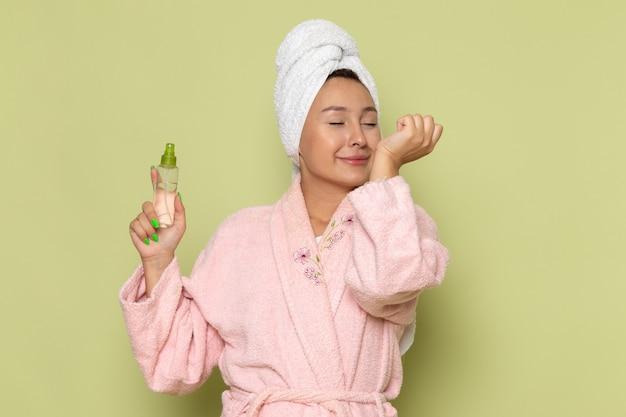 Female in pink bathrobe using little spray Free Photo