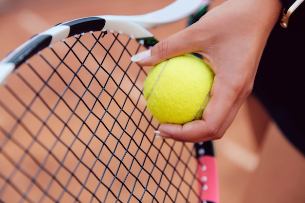 Female player's hand with tennis ball, preparing to serve during a match Free Photo