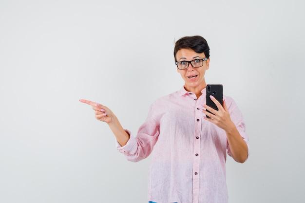 Женщина, указывая прочь, держа мобильный телефон в розовой рубашке и глядя возбужденным, вид спереди. Бесплатные Фотографии