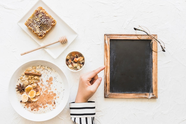 Female pointing finger at blank small blackboard with healthy breakfast; honeycomb and nuts Free Photo